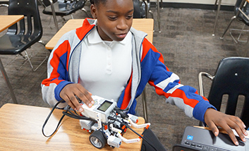 A girl programming a small robot