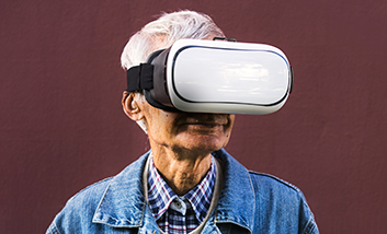 A senior man with a VR headset on